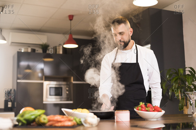 Confident chef with burning frying pan