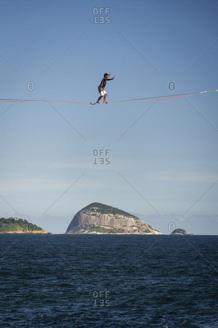 Rio de Janeiro, Brazil - March 31, 2019: Landscape of man on highline over ocean shore with rocky islands