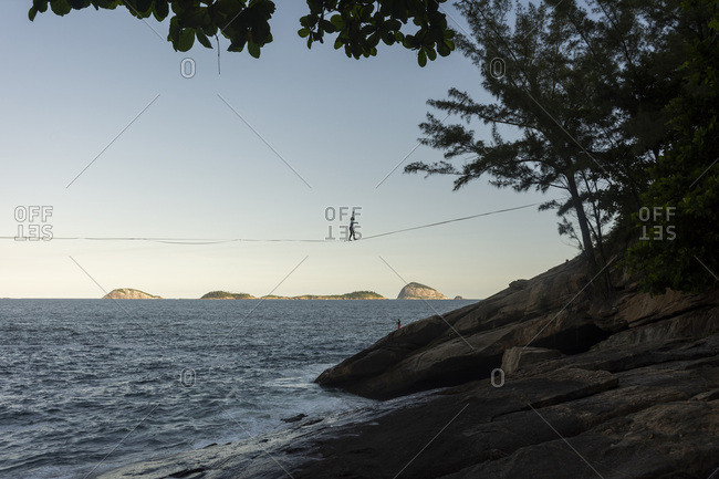 Landscape of man walking on highline over ocean with rocky islands