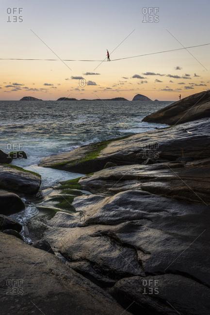 Beautiful landscape of man walking highline over ocean on rocky shore