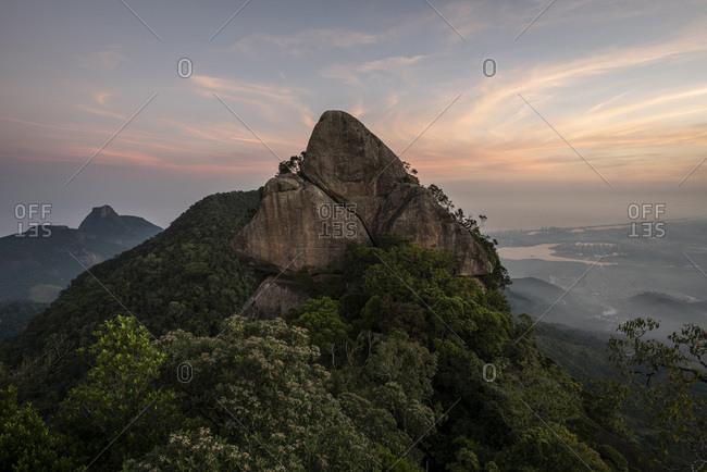 Beautiful landscape of rocky mountain peak on rainforest sunset