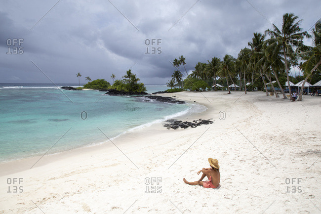 One man with hat and bathing suit, on sandy beach of samoa
