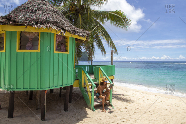 One man, reading a book on staircase of colorful beach hut, samoa