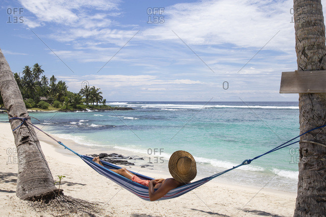 Man with hat, laying on blue hammock under palm trees at the beach