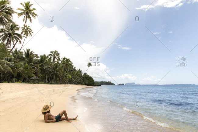 Latin man, wearing straw hat, tanning on golden sandy beach, samoa