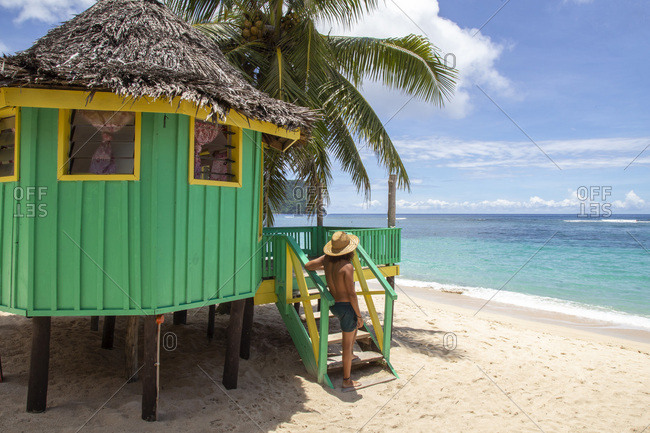 Man with hat, next to turquoise beach hut, during sunny day, samoa