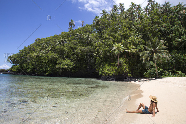 One fit man, wearing hat, tanning on tropical remote beach of samoa