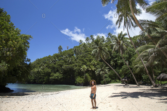 Man with sunglasses and straw hat, at tropical white sand beach, samoa
