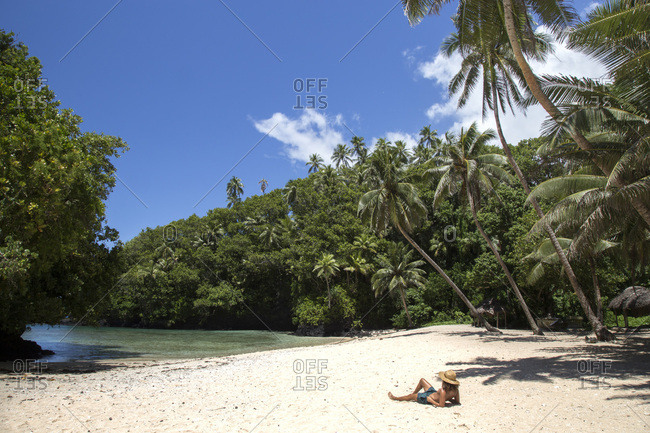 One man, tanning on tropical beach, under palm trees, during sunny day