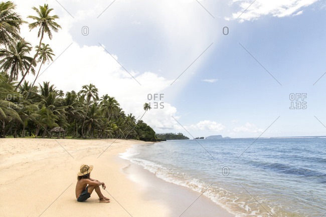 One man, wearing hat, relaxing at sandy tropical beach of samoa