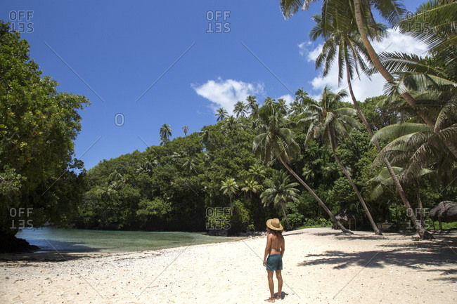 Latin guy, with hat and swimsuit, at tropical beach of south pacific