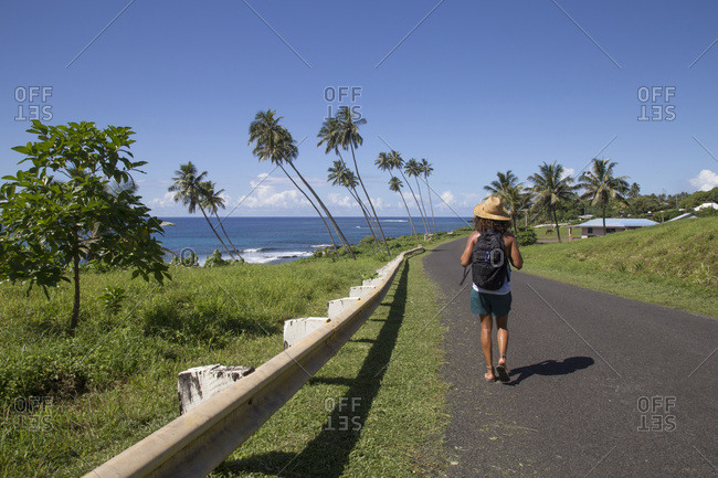 One tanned man, with black backpack, walking on coastline road, samoa