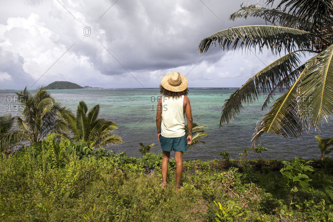Tanned man, staring at the reef and palm trees, during stormy day