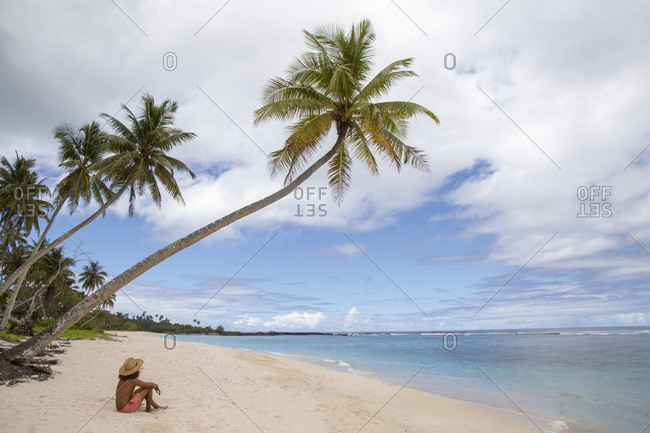 Man shirtless, in tropical beach, seated under leaning palm tree