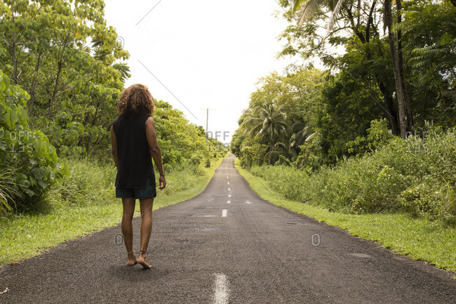 Man, with curly hair, wearing black singlet, walking on empty road