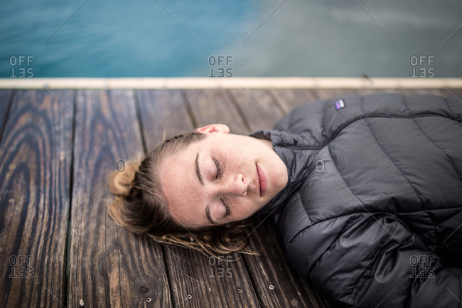 Woman takes a rest on a dock in maine