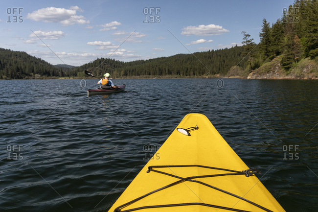 Kayaking in a yellow boat on couer d\'alene lake on a sunny spring day