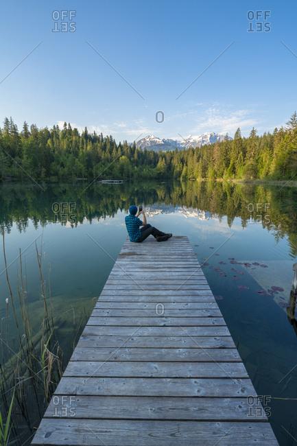 Man photographing crestasee lake with smartphone, switzerland