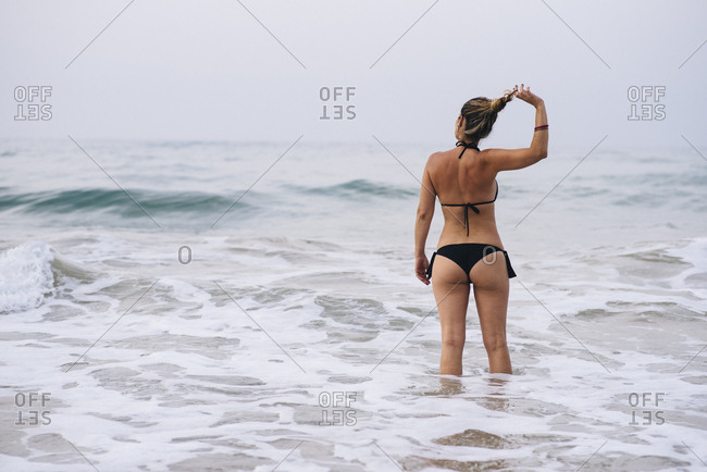 Back view of woman with black bikini arranging her hair on the beach.
