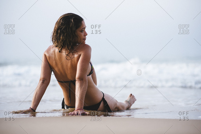 Woman with bikini sunbathing on the beach.
