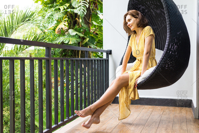 Young lady in yellow dress enjoying jungle view from the balcony