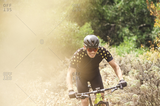 Upper body action photo of smiley male mountain bike cyclist in forest