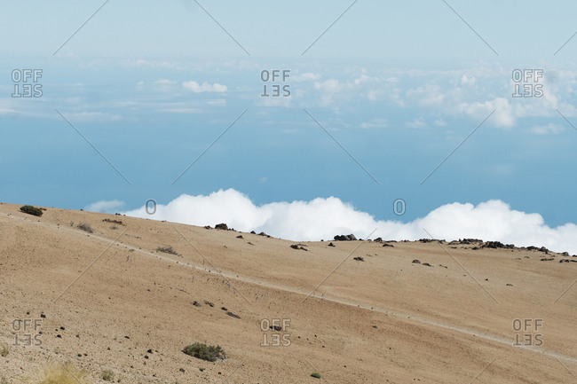 Minimalistic image of empty trail against blue sky over clouds