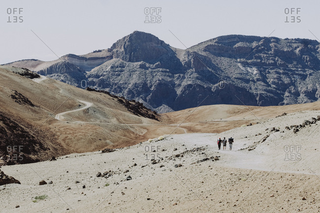 Three hikers walk on trail in rocky and volcanic landscape