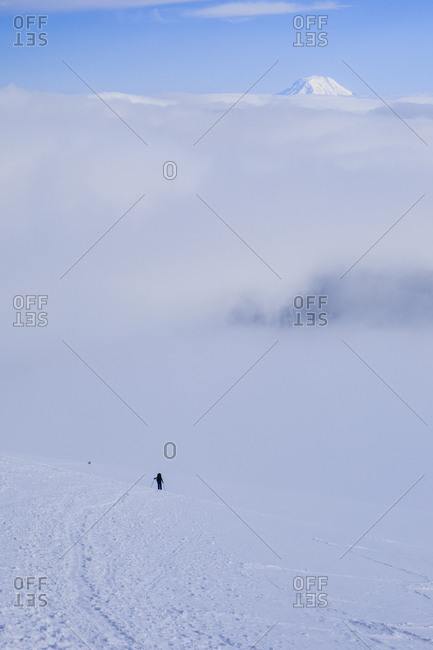 A lone climber nears mount rainier's camp muir with mt adams behind