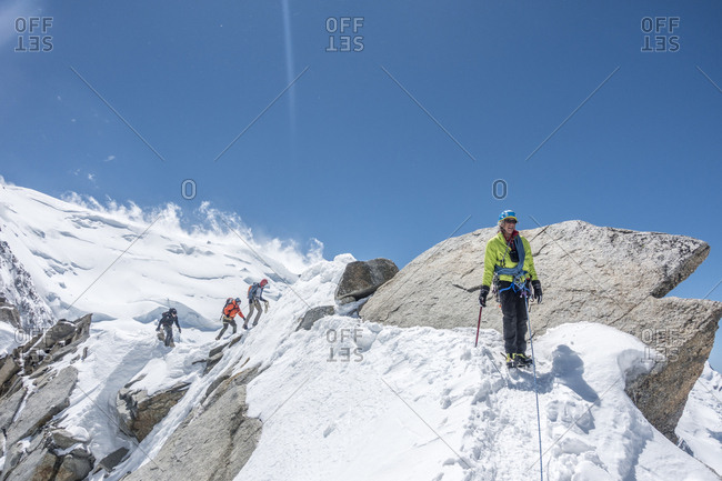 France, Auvergne-Rhone-Alpes, Chamonix - June 13, 2019: A senior climber walks across a ridge with a rope team in the back