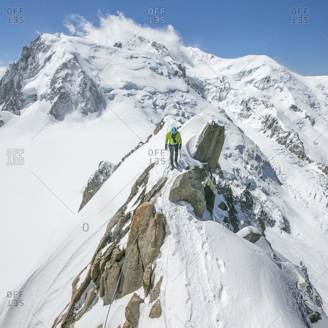 A male alpinist heads across an exposed knife-edge ridge on mt blanc