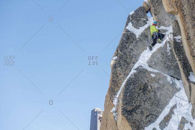 An alpinist runs out steep mixed terrain on the aiguille du midi