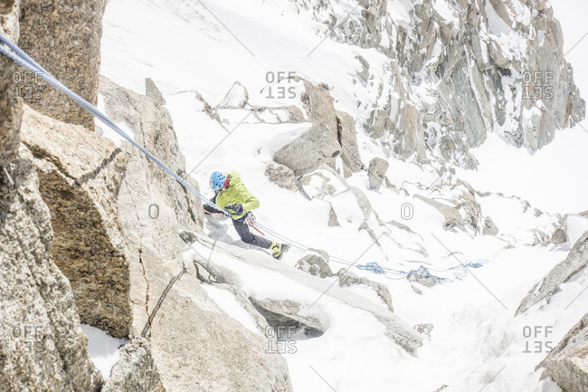 Alpinist on rappel in a steep mixed snow and rock cliff on mont blanc