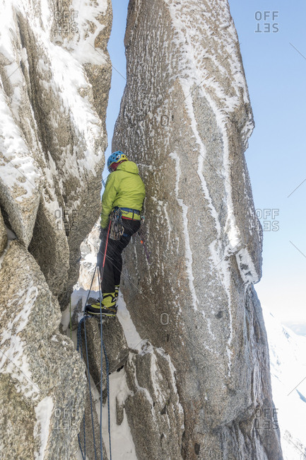 Alpinist navigates a chimney between 2 grime crusted mt blanc spires