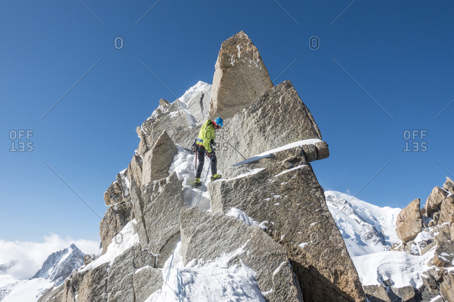 Alpinist rappels a short rock step on the cosmiques ridge