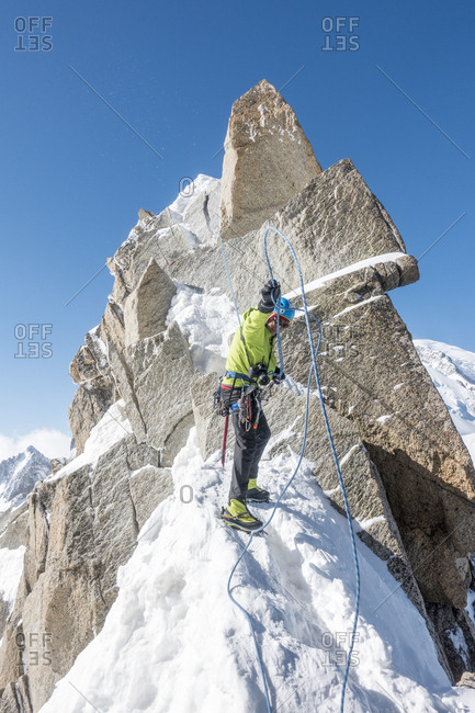 Alpinist manages his ropes after completing a short rappel