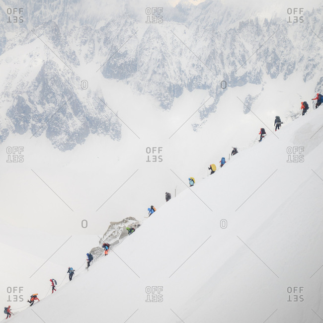 Traffic jam on mt blanc as a string of climbers navigate a steep ridge