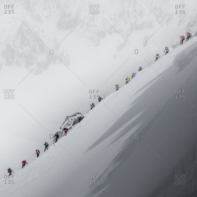 Traffic jam on mt blanc as a string of climbers navigate a steep ridge