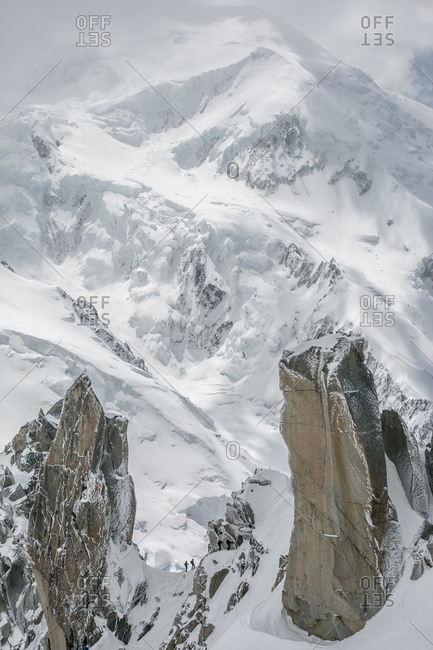 Two alpinists on cosmiques are dwarfed by mt blanc in the background