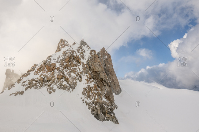 The famous aiguille du midi amid clouds in late evening light