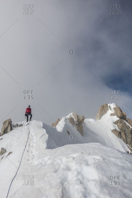 An alpinist poses on a ridge after summiting aiguille du chardonnet