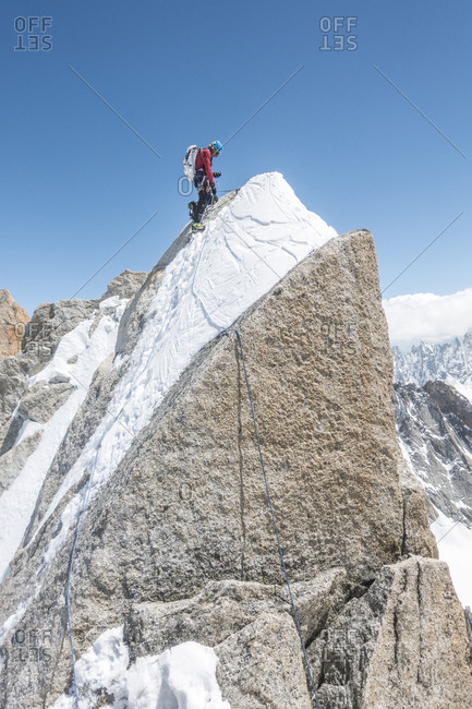An alpinist considers his anchor setup before committing to a rappel