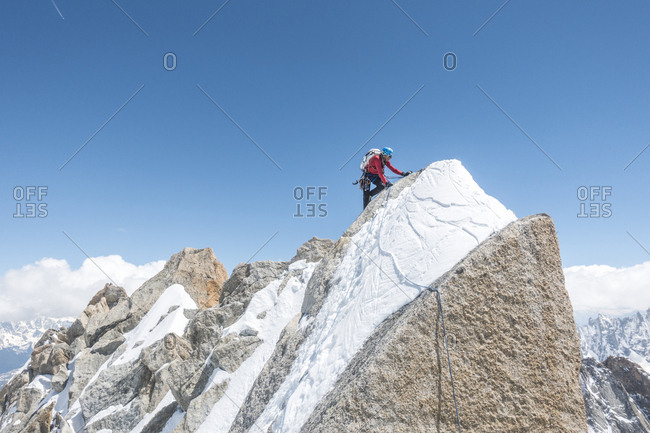 Alpinist in red shirt high up on a mixed terrain alpine ridge
