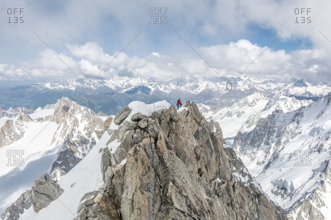 Alpinist poses high up on the famous forbes arete in the french alps