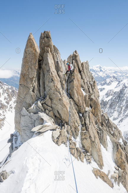 A seasoned alpinist rappels a spectacular gendarme on the forbes ridge