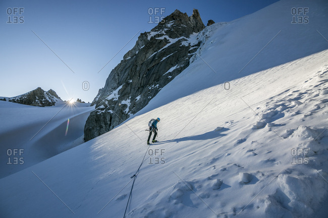 An alpinist tackles a steep snow slope as the sun crests the horizon