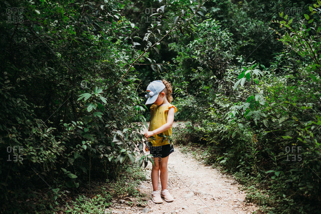 Young girl wearing rainbow hat hiking through trees