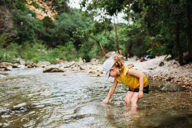 Young girl putting hand in water at barton springs on a hot summer day