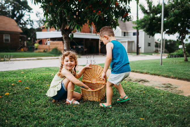Young girl smiling with basket full of peaches in front yard