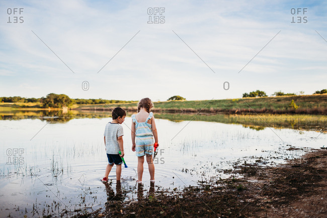 Young boy and girl looking for fish with nets in lake